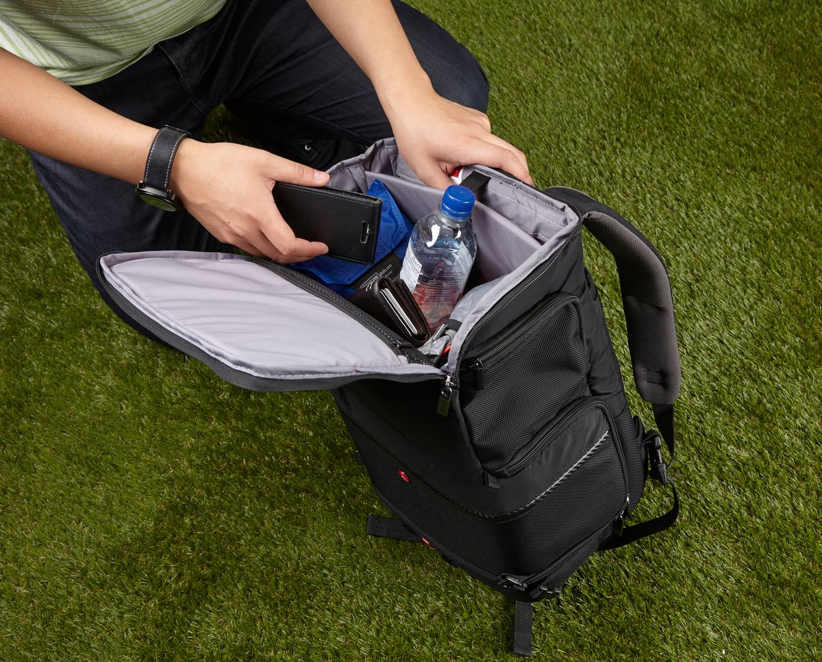 A man packs a water bottle, phone, and wallet into his backpack.