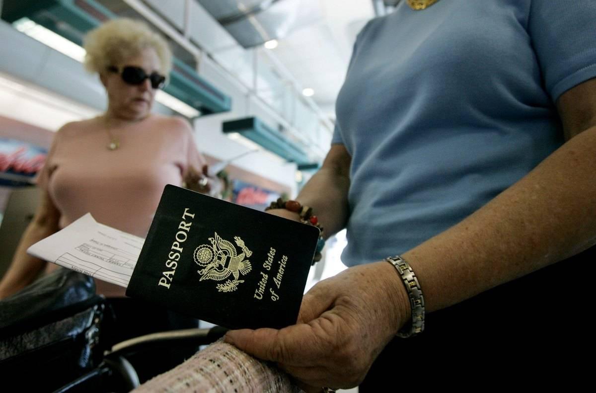 A man checks his passport while in an airport.