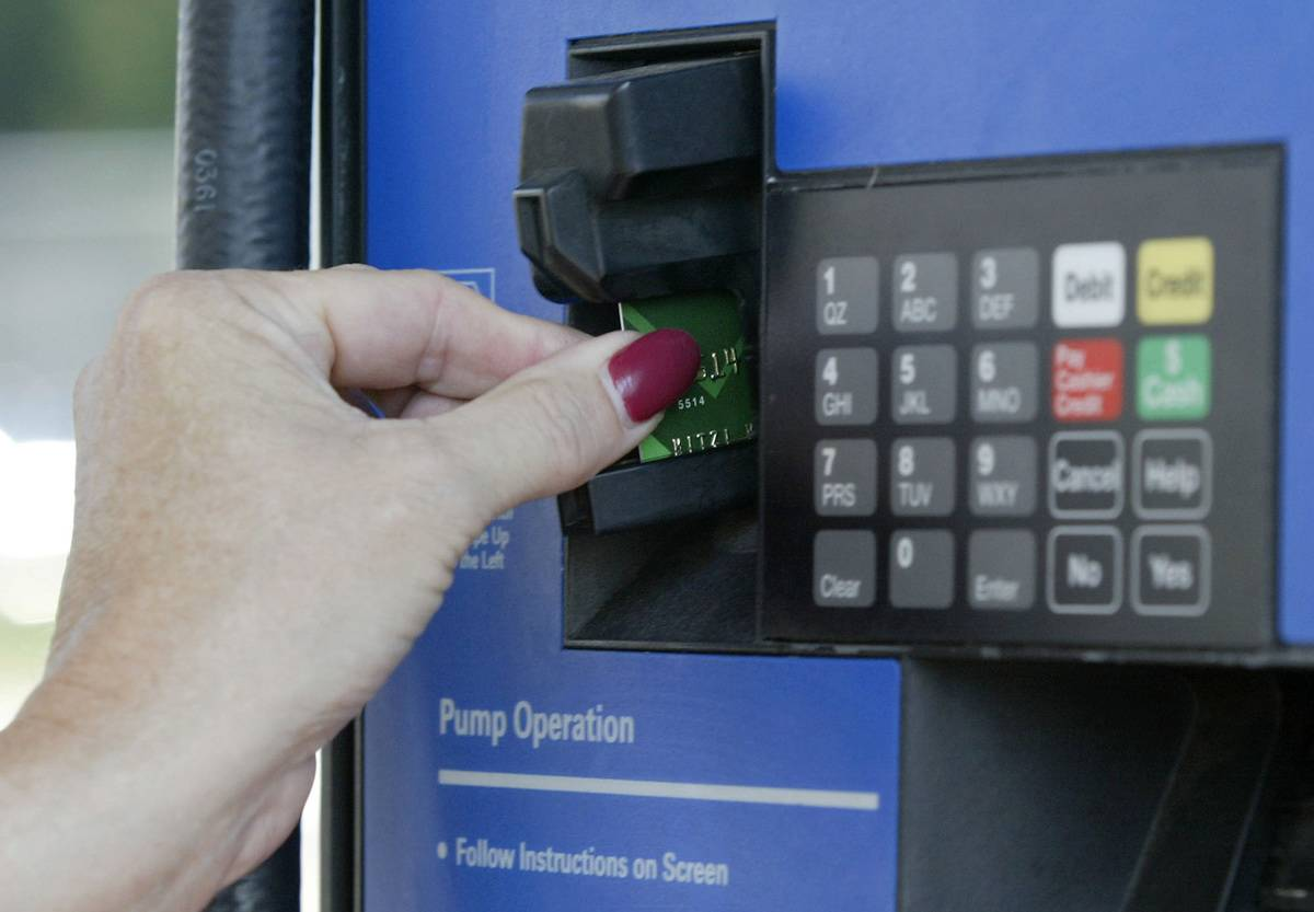 A woman uses a credit card to pay for gas at a station.