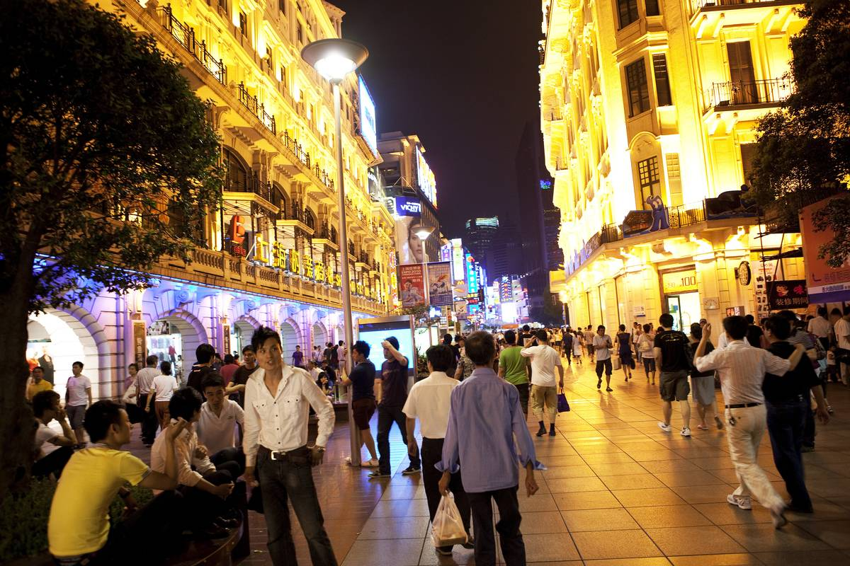 Shoppers walk along Nanjing East Road, a pedestrian street and one of the main shopping districts in Shanghai, China.