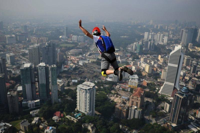A person base jumps off of a 300-meter high skyscraper in Malaysia.