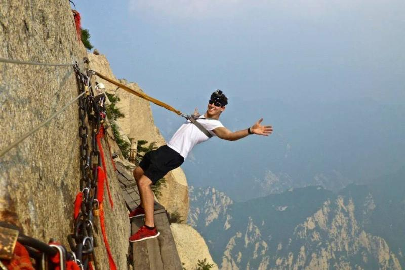 A hiker dangles off the narrow Plank Walk of the Hua Shan Trail in China.