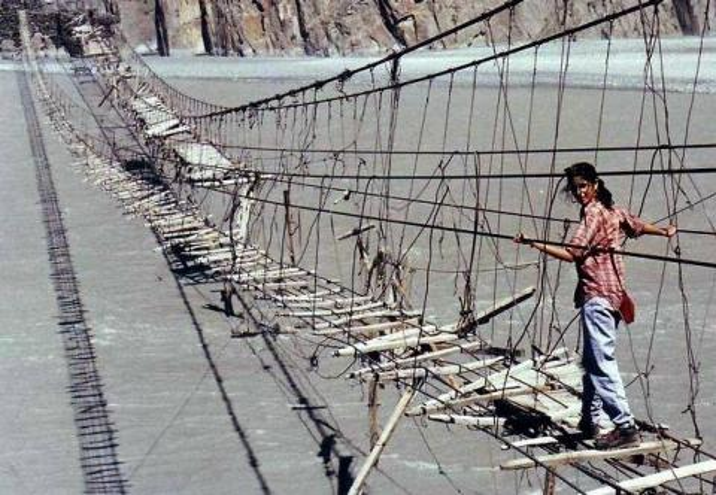 A woman crosses the broken planks of the Hussaini Hanging Bridge.