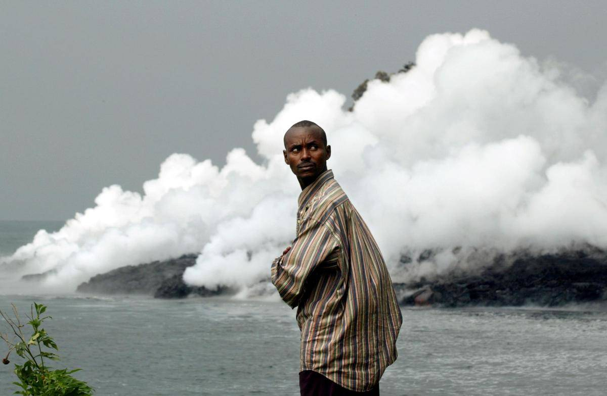 A man stands by Lake Kivu, which steams as lava from the nearby volcano Niragongo pours in.