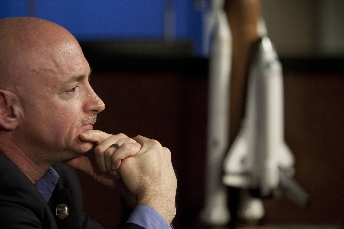 Mark Kelly sits and ponders next to a statue of a rocket.