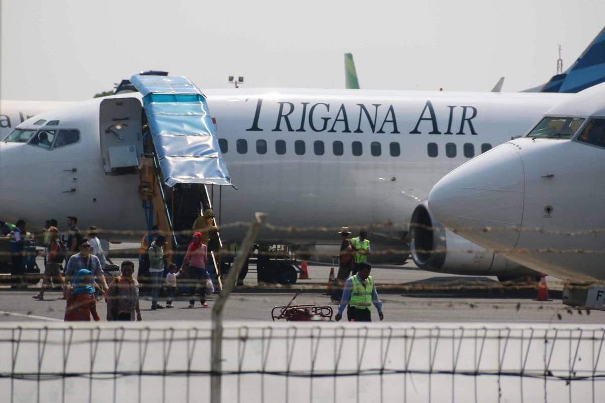 Passengers exist a Trigana Air plane.