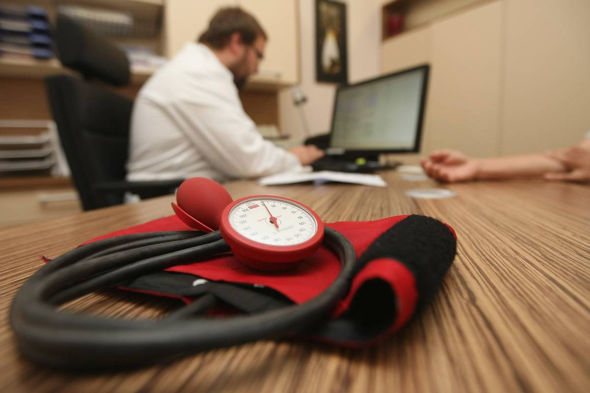 A doctor speaks to a patient as a sphygmomanometer, or blood pressure meter, lies on his desk.