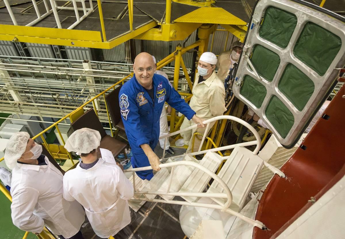 Scott Kelly climbs stairs to enter the Soyuz TMA-16M spacecraft.