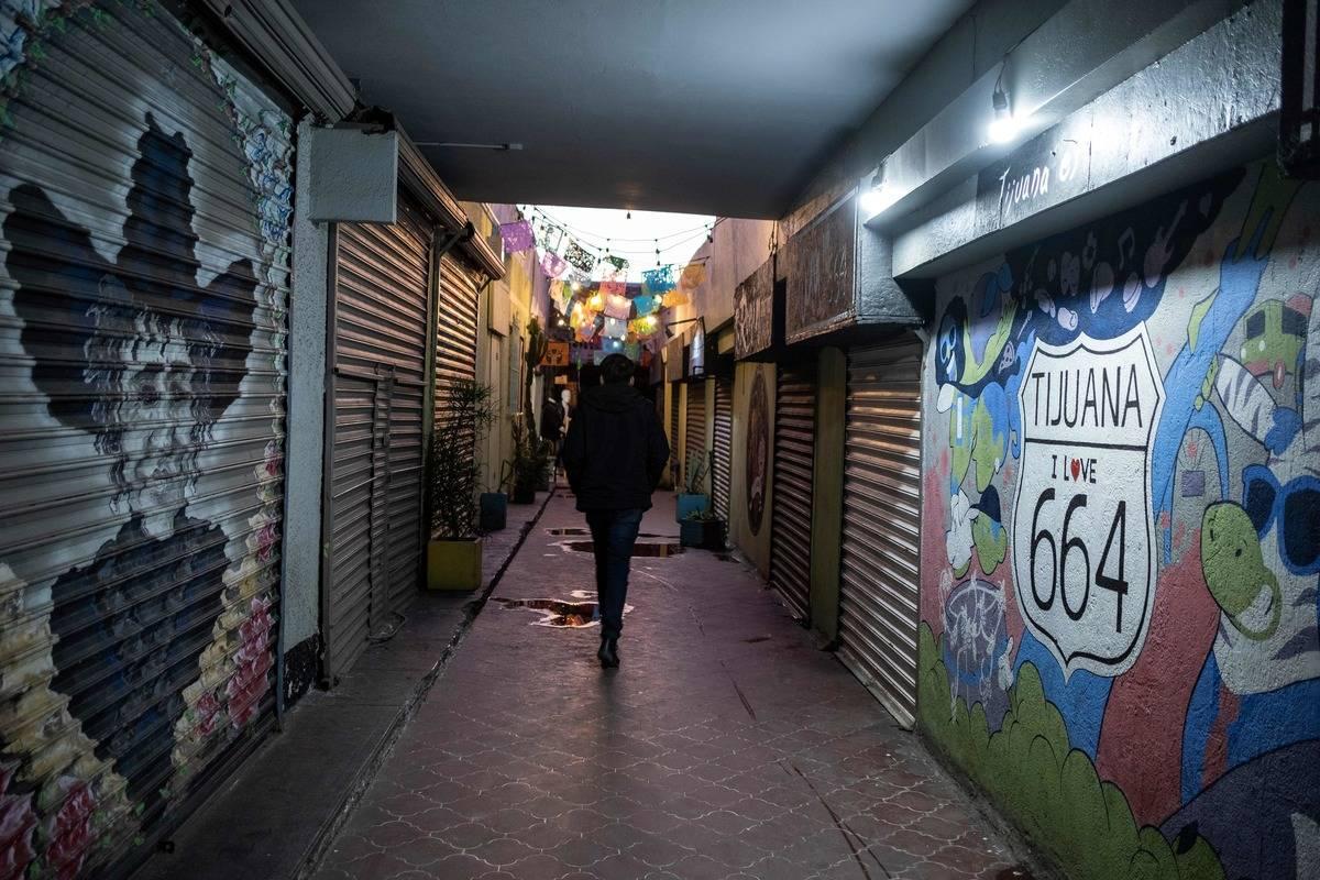 A man walks through a closed food court in Tijuana.