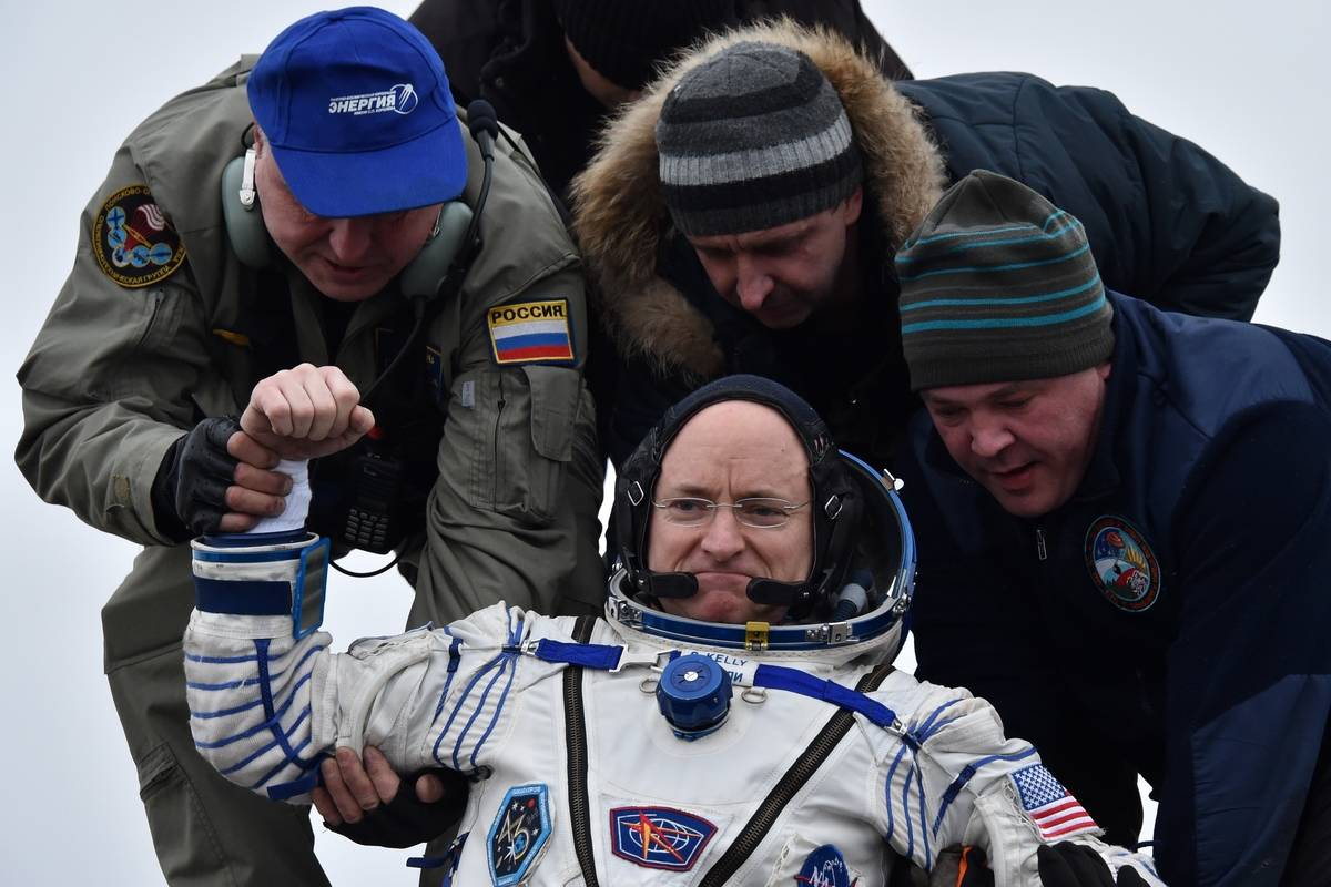Three men help Scott Kelly get out of a space capsule.