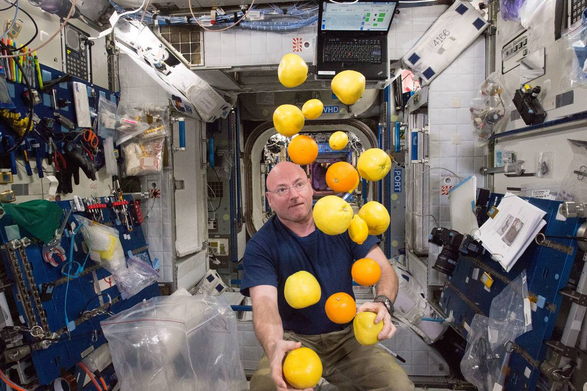 In this International Space Station, Scott Kelly juggles fresh fruit that arrived for his crew.
