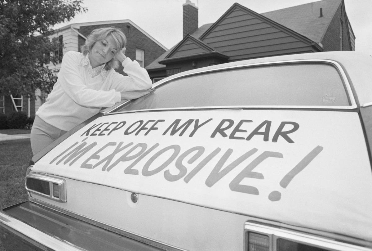 A woman leans on her Ford Pinto with a sign that says,