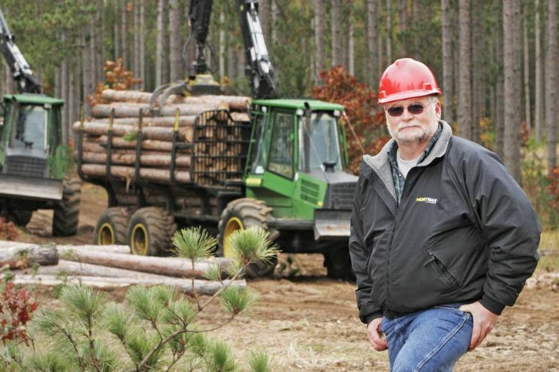 An employee stand in front of a timber harvesting truck.