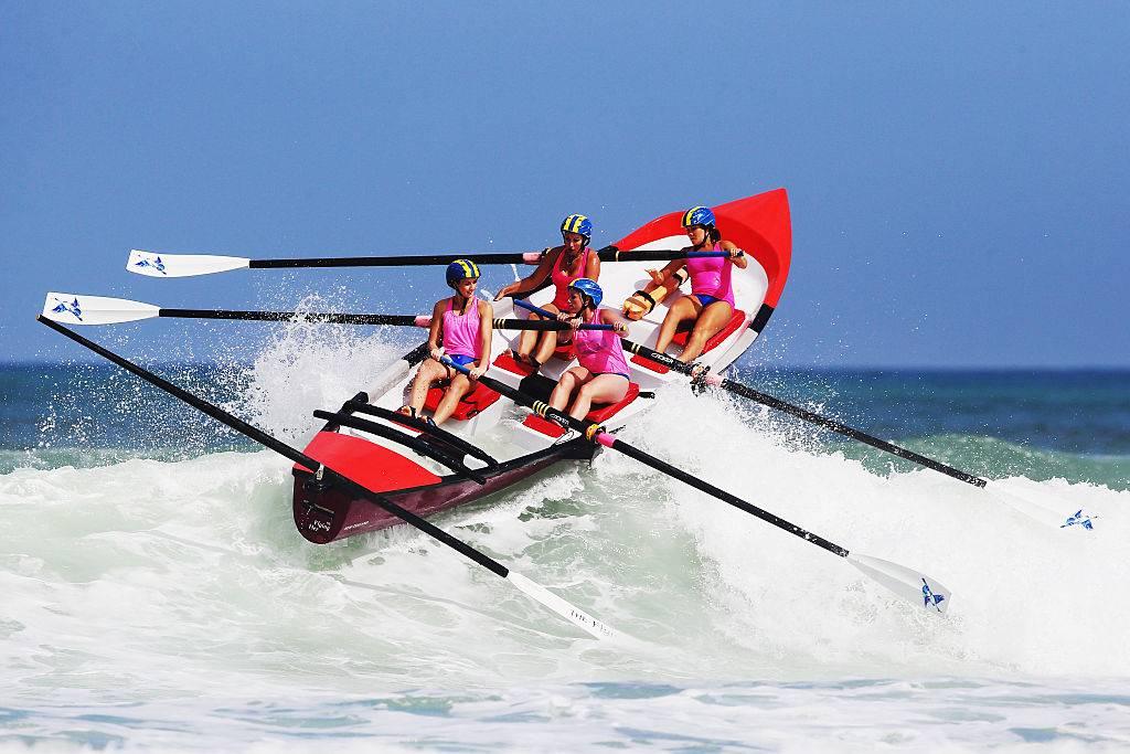 four women rowing a boat in piha, new zealand