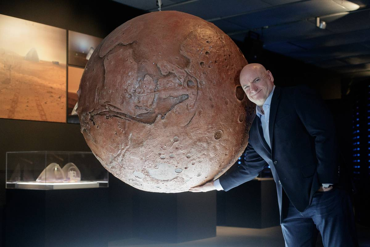 Scott Kelly stands next to a model of the planet Mars.