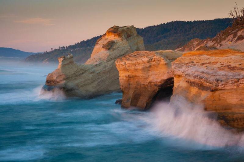 Waves crashing on cliffs at sunset in Tillamook Coast, Oregon