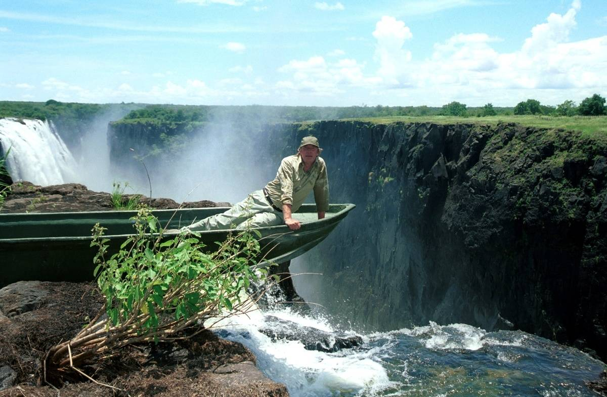 A man sits in a boat that sits in Devil's Pool and leans over Victoria Falls.