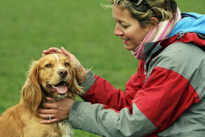 woman petting a dog outside