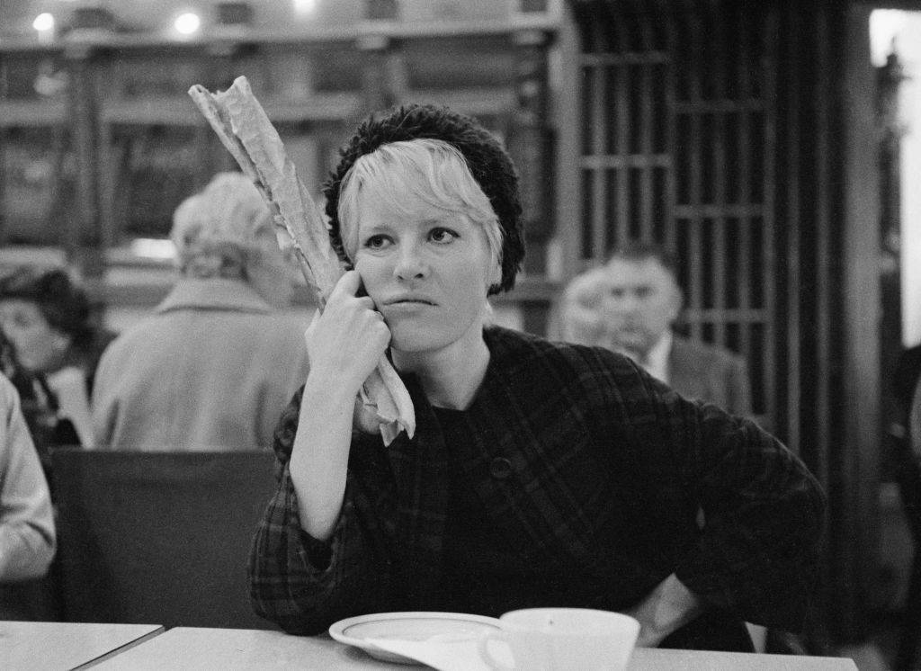 Petula Clark holding a baguette at a dinner table