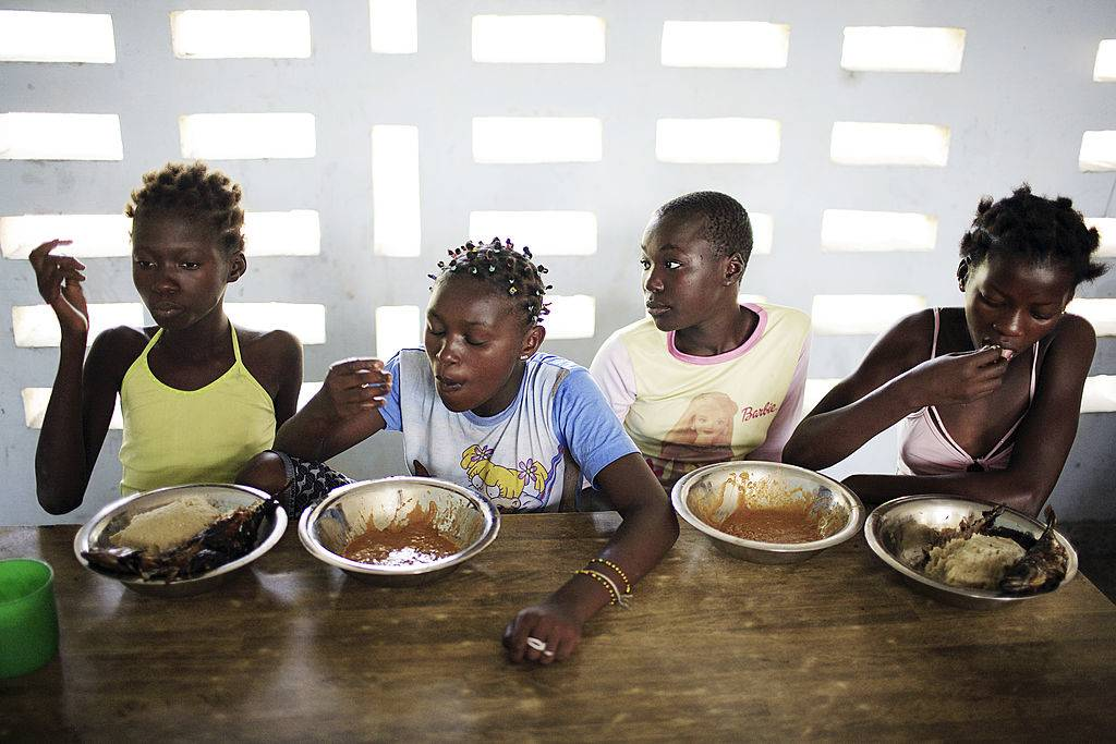 four girls eating food with their right hands
