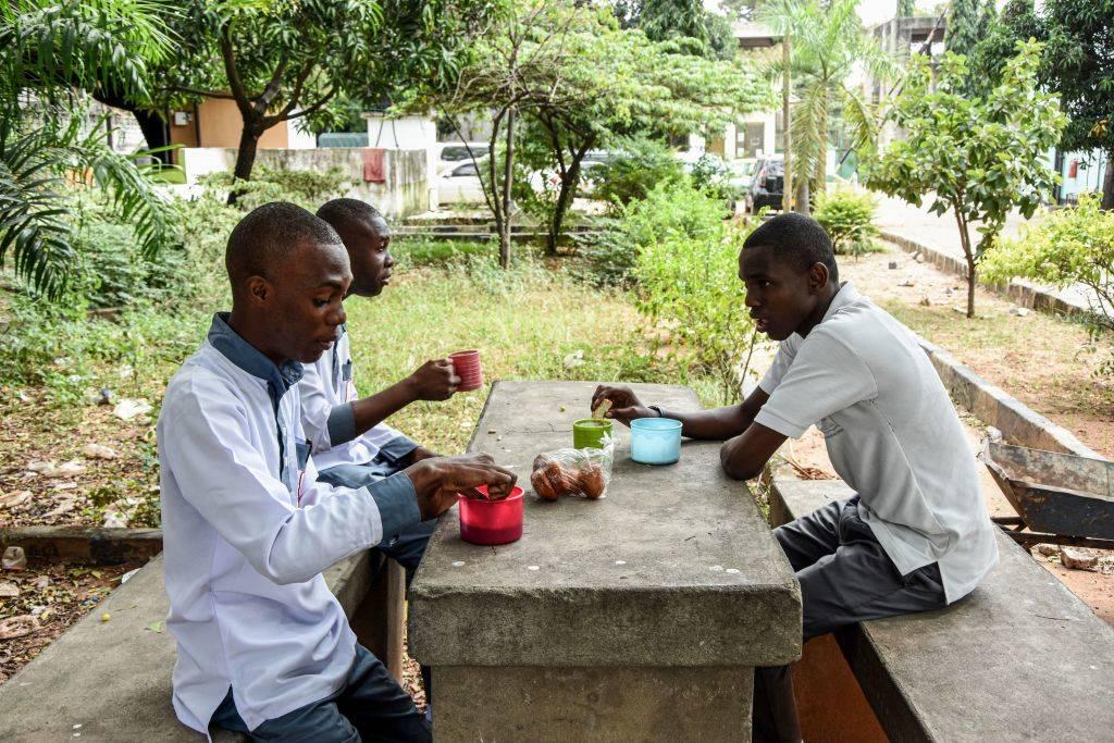 three men eating food in tanzania