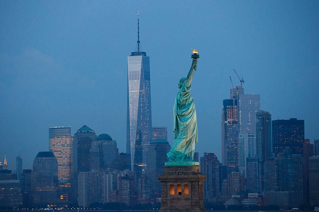 The Statue of Liberty stands in the foreground of Lower Manhattan