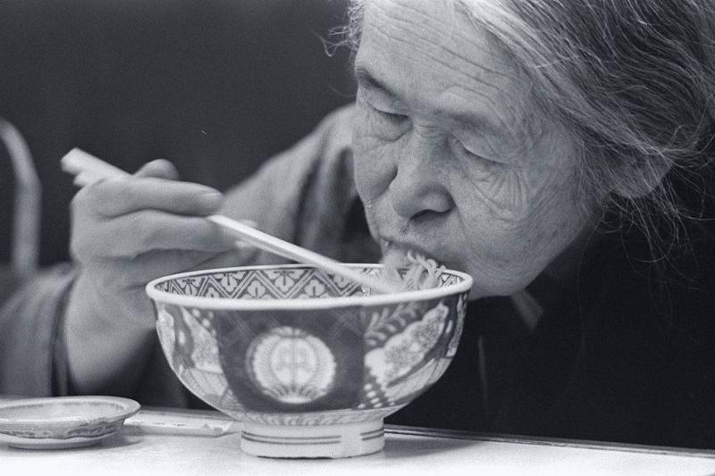 elderly japanese woman eating noodles